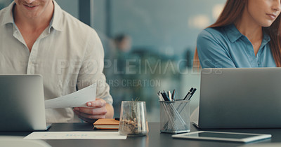 Buy stock photo Closeup shot of two unrecognisable businesspeople working together in an office