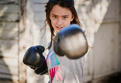 Buy stock photo Portrait of a young girl practicing a boxing routine in the garden at home