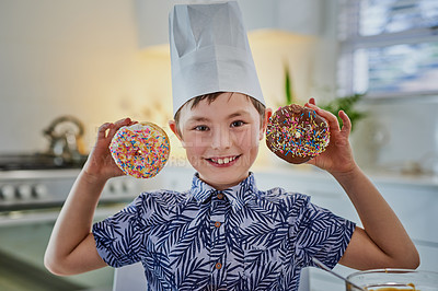 Buy stock photo Shot of an adorable little boy making doughnuts at home