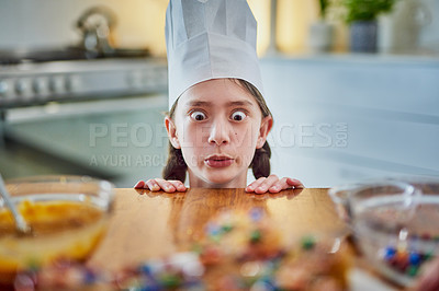 Buy stock photo Shot of a cute young girl staring at freshly baked cupcakes on the kitchen counter at home