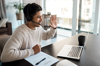 Buy stock photo Shot of a young man wearing a headset while making a video call on a laptop at home