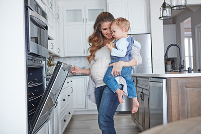 Buy stock photo Shot of a pregnant woman baking while spending spending time with her toddler son at home
