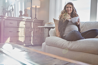 Buy stock photo Full length shot of an attractive young pregnant woman eating breakfast while sitting on the sofa at home