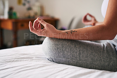 Buy stock photo Shot of a young woman meditating while sitting at home