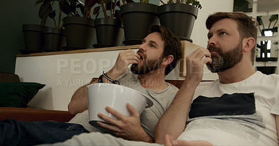 Buy stock photo Shot of a mature couple having popcorn while watching tv at home
