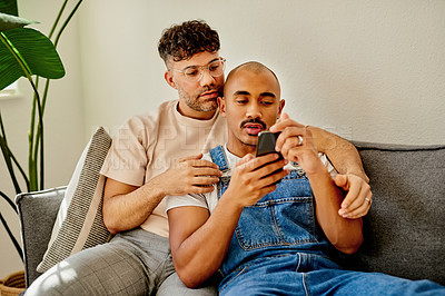 Buy stock photo Shot of a couple looking at something on a cellphone while sitting together at home