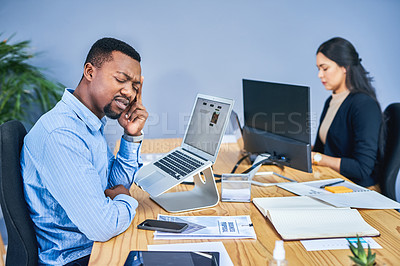 Buy stock photo Shot of a young businessman suffering with a headache while working in an office with a colleague in the background