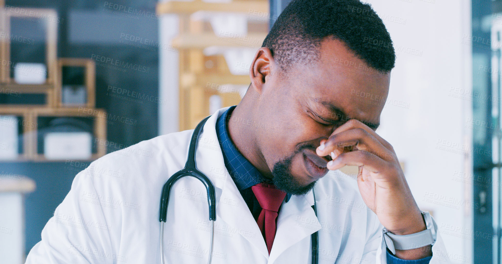 Buy stock photo Shot of a young doctor looking stressed out while working in a modern hospital