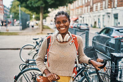 Buy stock photo Shot of a young woman riding her bicycle through the city