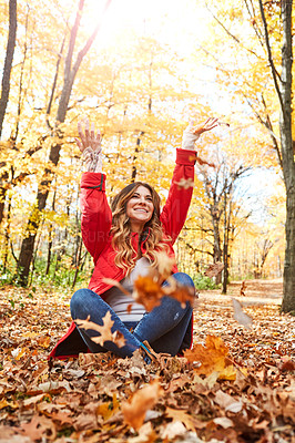 Buy stock photo Full length shot of an attractive young woman throwing leaves while sitting in the forest during autumn