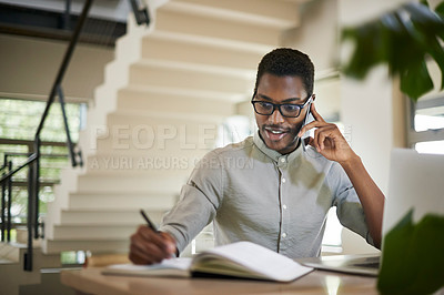 Buy stock photo Shot of a young man talking on a cellphone while writing notes at home