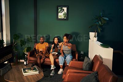 Buy stock photo Shot of three friends having snacks and drinks while enjoying a movie night