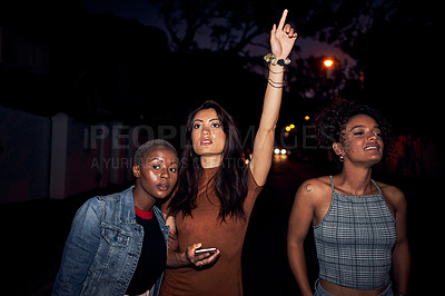 Buy stock photo Cropped shot of three women hailing a cab while out together at night