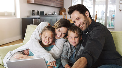 Buy stock photo Shot of a happy young family using a digital tablet on the sofa at home