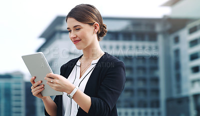 Buy stock photo Shot of a young businesswoman using a digital tablet in the city