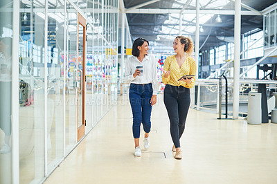 Buy stock photo Shot of two young businesswomen having a discussion while walking through a modern office
