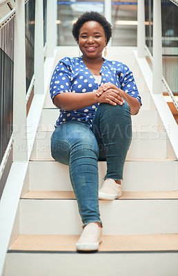 Buy stock photo Portrait of a confident young businesswoman sitting on the steps of a modern office