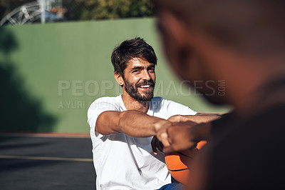 Buy stock photo Shot of a sporty young man giving his teammate a fist bump on a basketball court