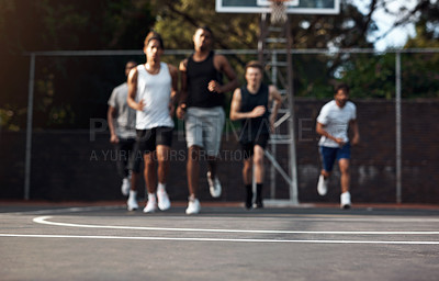Buy stock photo Defocused shot of a group of sporty young men running on a sports court