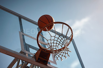 Buy stock photo Closeup shot of a basketball landing into a net on a sports court