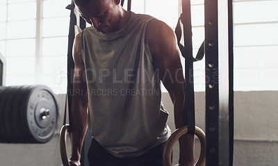 Buy stock photo Shot of a young man exercising with gymnastic rings in a gym