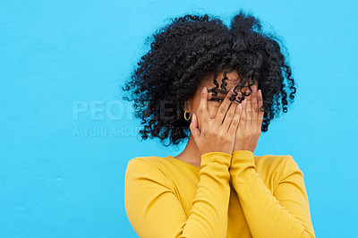 Buy stock photo Shot of a young woman peeking through her fingers while posing against a blue background