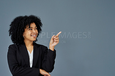 Buy stock photo Shot of a confident young businesswoman pointing against a grey studio background