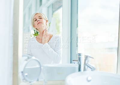 Buy stock photo Shot of a mature woman applying moisturiser to her neck in a bathroom at home