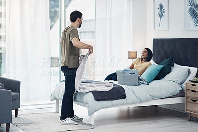 Buy stock photo Shot of a young man folding laundry while his wife relaxes on the bed at home