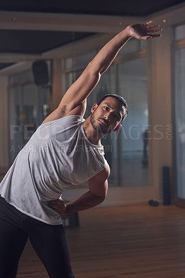 Buy stock photo Cropped shot of a handsome young male athlete going through his warmup routine in the gym