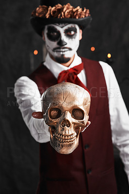 Buy stock photo Cropped portrait of a handsome young man dressed in his Mexican-style halloween costume holding out a skull