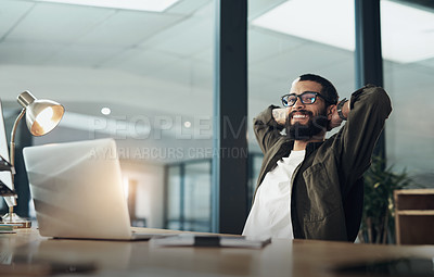 Buy stock photo Shot of a young businessman taking a break while working late at night in a modern office