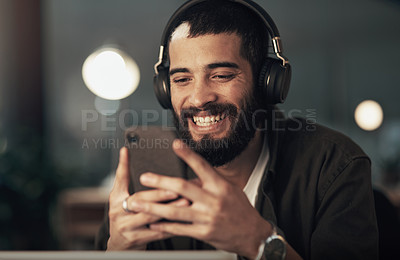 Buy stock photo Shot of a young businessman using a smartphone with headphones during a late night at work