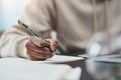 Buy stock photo Shot of an unrecognisable man writing in a notebook while working from home
