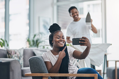 Buy stock photo Shot of a young woman taking selfies while her husband irons clothing in the background