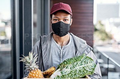 Buy stock photo Shot of a young man delivering fresh produce to a place of residence