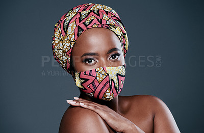 Buy stock photo Studio portrait of a beautiful young woman wearing a mask against a grey background
