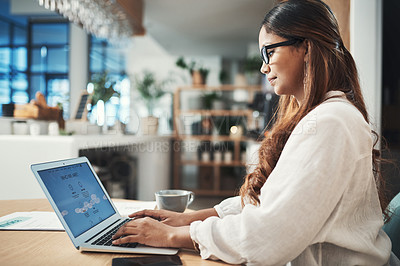 Buy stock photo Shot of a businesswoman using her laptop while working at a cafe