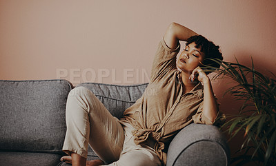 Buy stock photo Shot of a beautiful young woman relaxing on the sofa at home