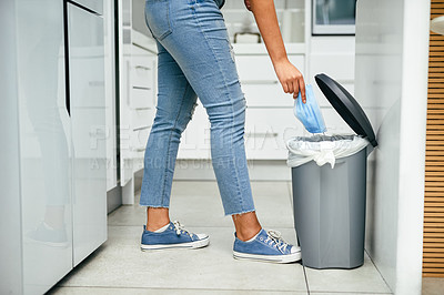 Buy stock photo Closeup shot of an unrecognisable woman disposing a mask in a bin at home