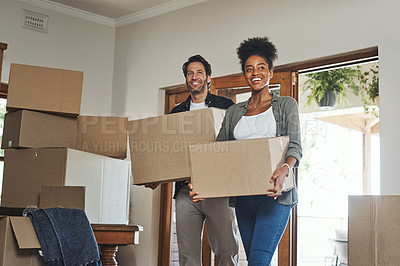 Buy stock photo Shot of a young couple smiling while carrying boxes into their new home