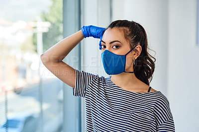 Buy stock photo Shot of a masked young woman standing next to a window