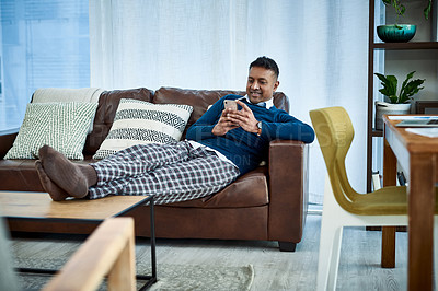 Buy stock photo Shot of a man using a smartphone on the sofa at home