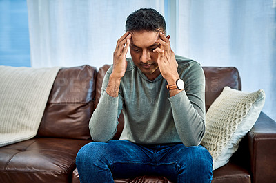 Buy stock photo Shot of a man looking stressed while sitting on the sofa at home