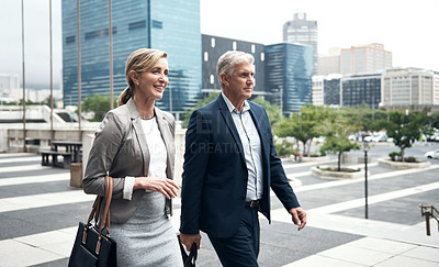 Buy stock photo Shot of two mature businesspeople walking in the city