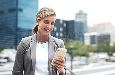 Buy stock photo Shot of a mature businesswoman using a cellphone in the city