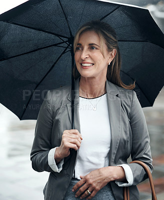 Buy stock photo Shot of a mature businesswoman holding an umbrella while out in the city