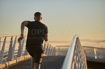 Buy stock photo Rearview shot of a sporty young man running on a bridge in the city