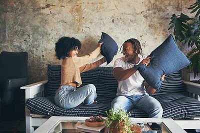 Buy stock photo Shot of a young couple having a pillow fight while relaxing together on a sofa at home