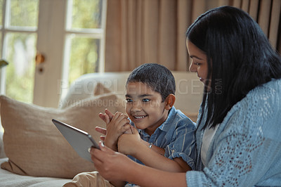 Buy stock photo Shot of a young boy using a digital tablet while sitting at home with his mother